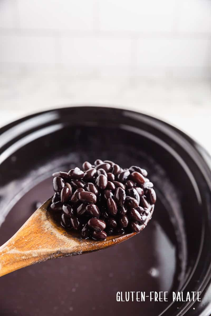 a wooden spoon full of crockpot black beans