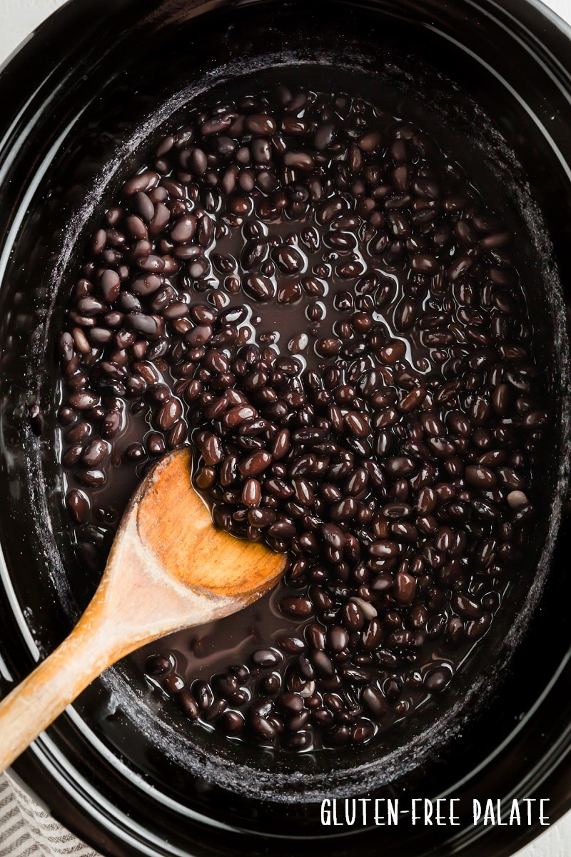 top down view of black beans in a crockpot with a wooden spoon