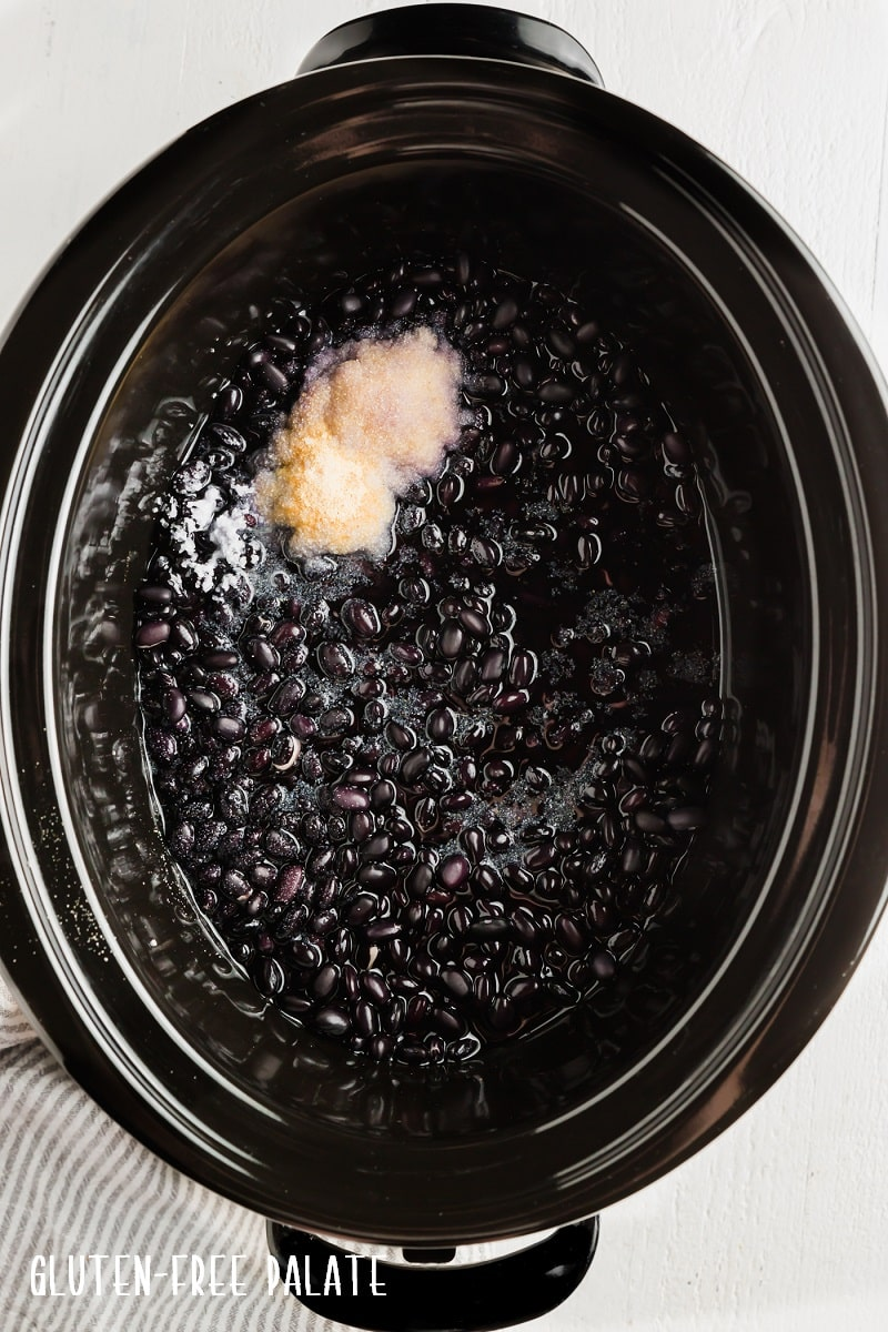 top down view of black beans and seasonings in a slow cooker