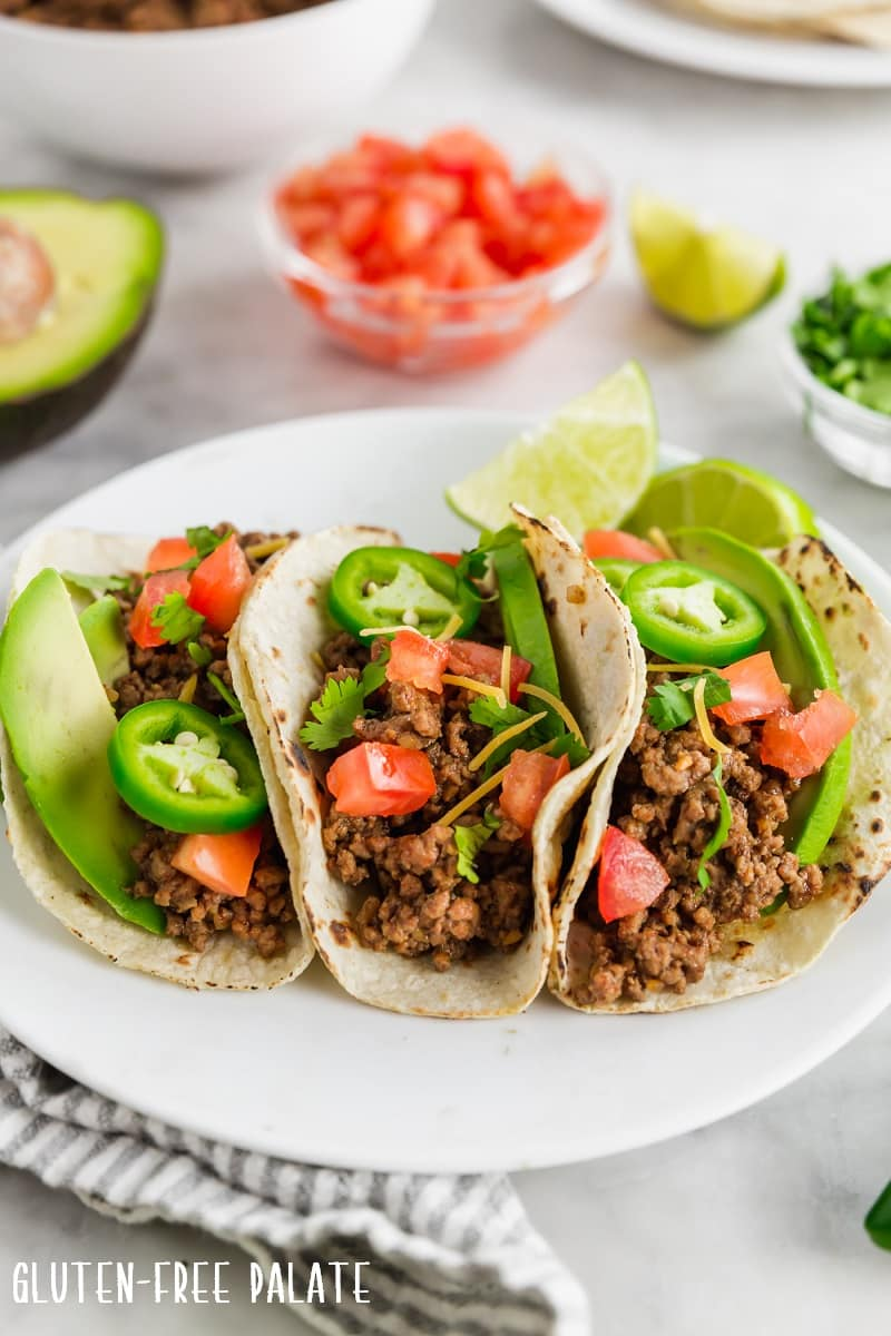three gluten free tacos on a white plate
