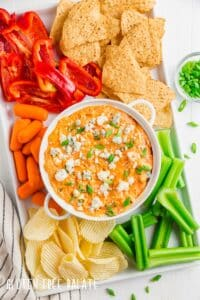 top down view of instant pot buffalo chicken dip in a white bowl with sliced veggies
