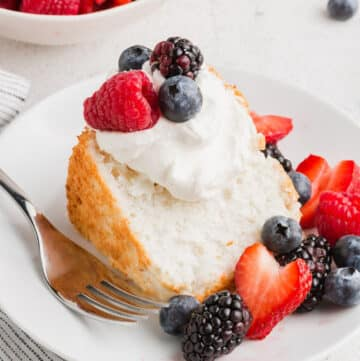 a slice of gluten free angel food cake with whipped cream and berries