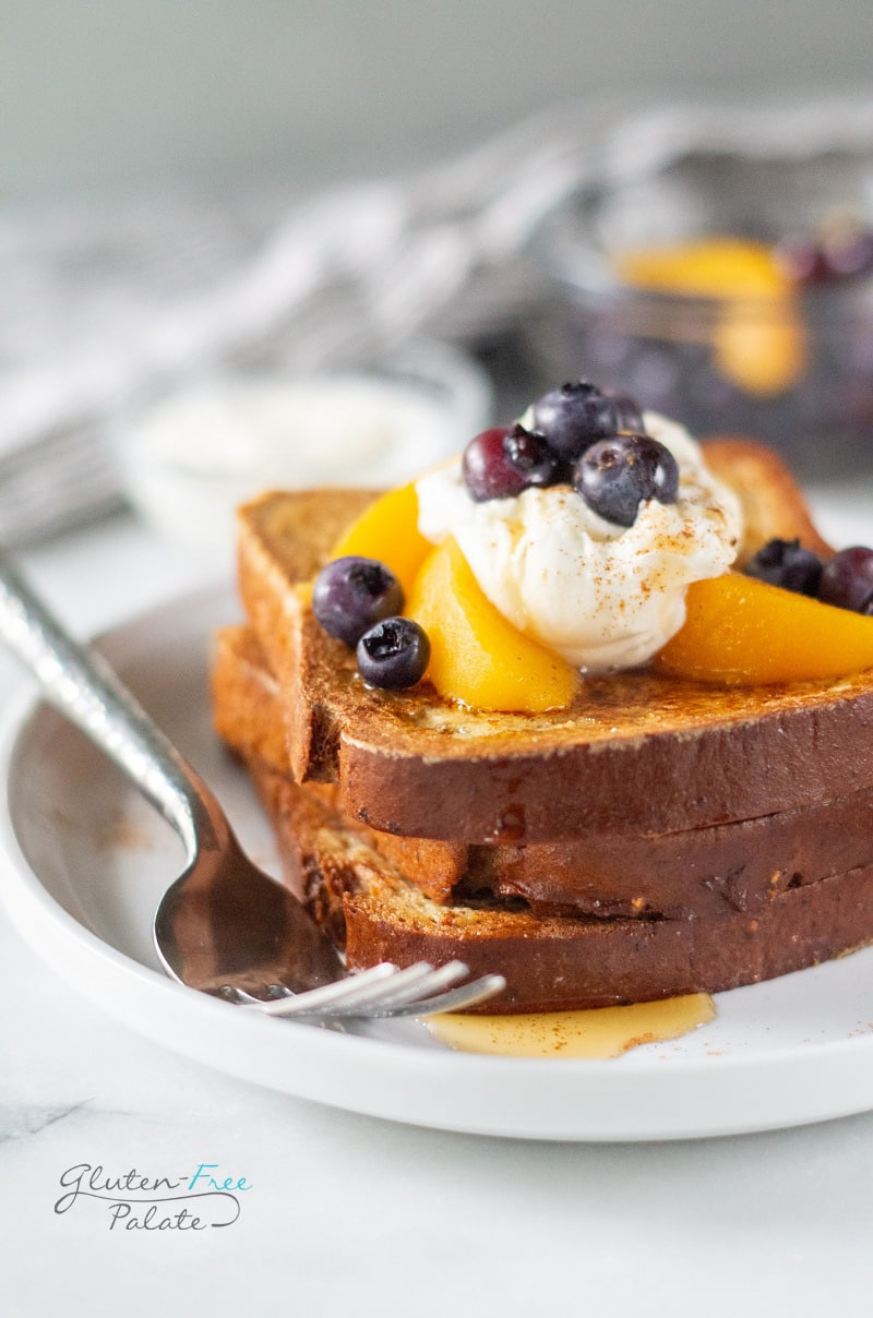 close up of two slices of gluten free French toast on a white plate with a fork
