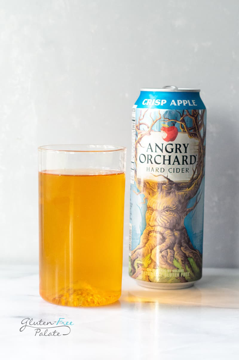 A glass of gluten free hard cider next to a can