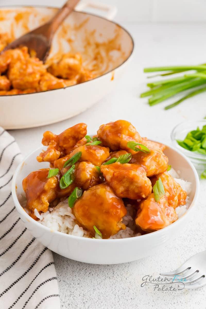 gluten free orange chicken over rice in a white bowl