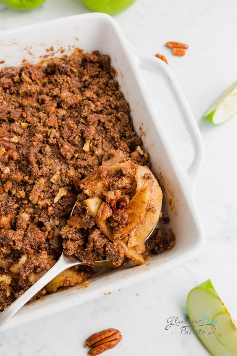 a spoon taking a serving of paleo apple crisp from the pan