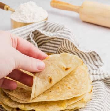 a hand folding up a gluten free tortilla