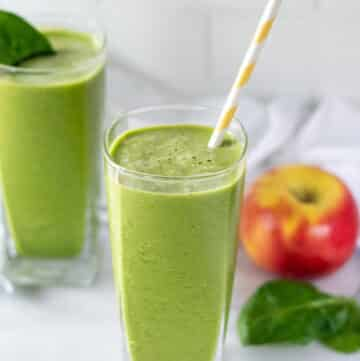apple spinach smoothie in a glass with a yellow striped straw