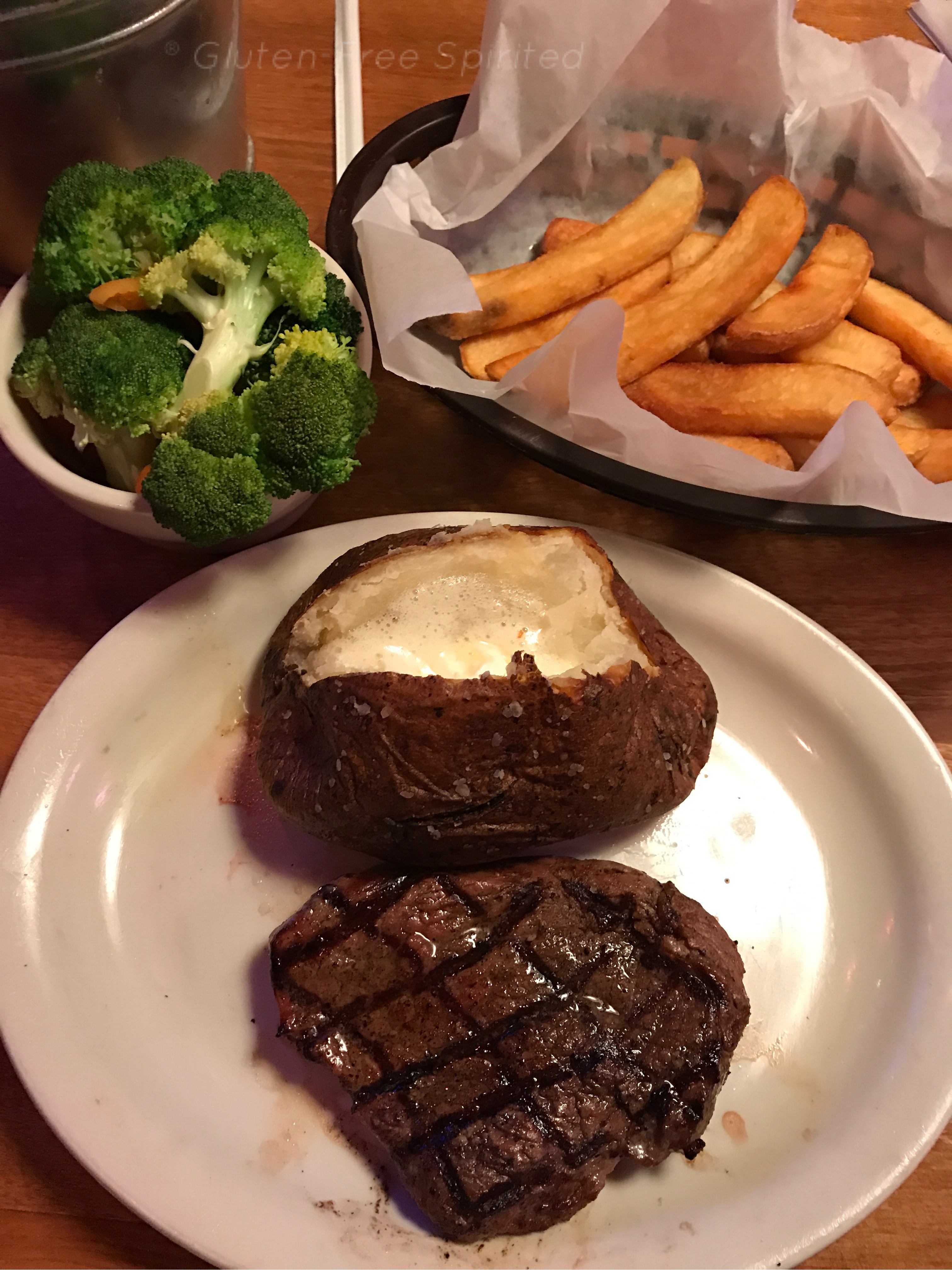 An image of steak, baked potato, broccoli & carrots, and french fries.