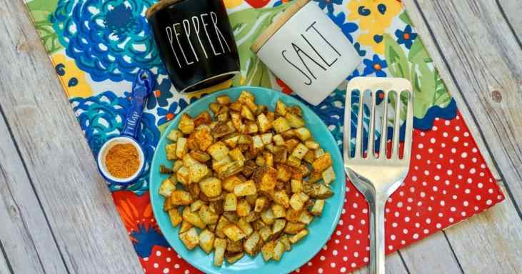 air fryer cajun diced potatoes on plate with other table decor