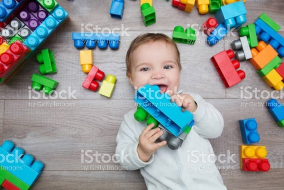 Toddler in childcare surrounded by blocks