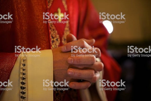 Catholic priest at Mass praying
