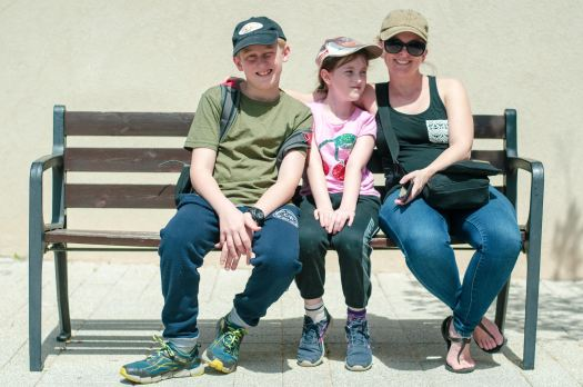 An image of mom and kids sitting on a bench in front of a plain boring wall