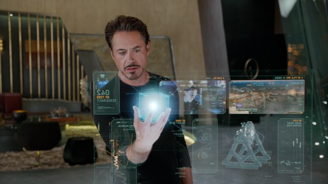 The character Tony Stark from the Avengers movie holds a 3d hologram cube surrounded by other holographic displays