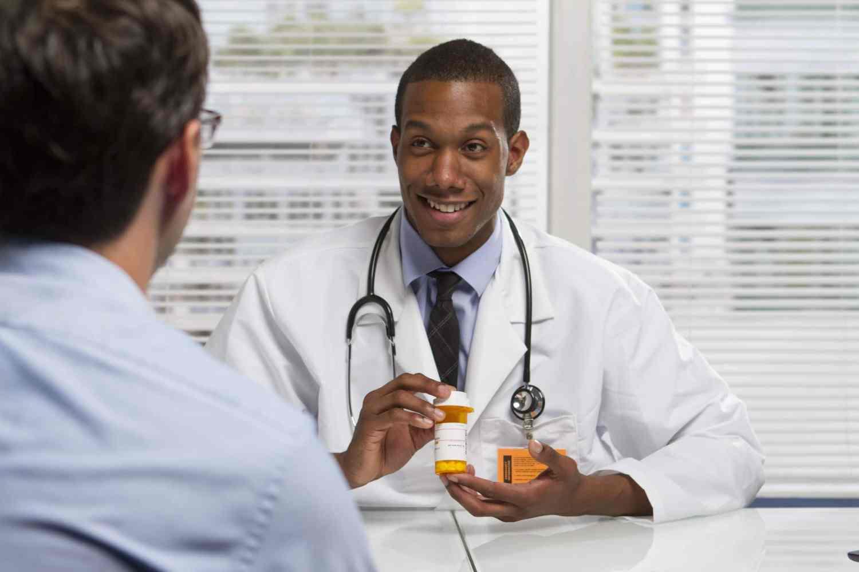 22665451 – young black doctor showing patient prescription, horizontal