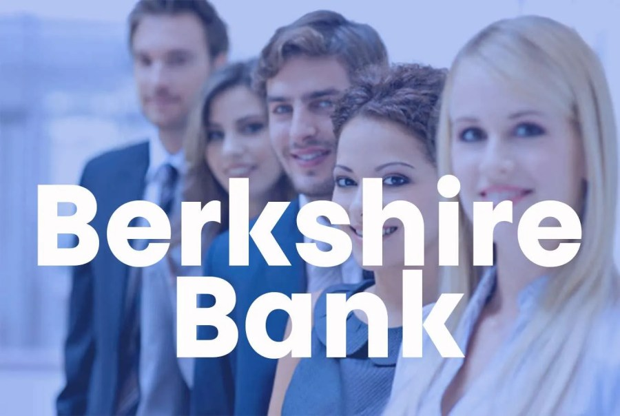 """A group of businesspeople stand in a row and look at the camera with the super """"Berkshire Bank"""" across"""