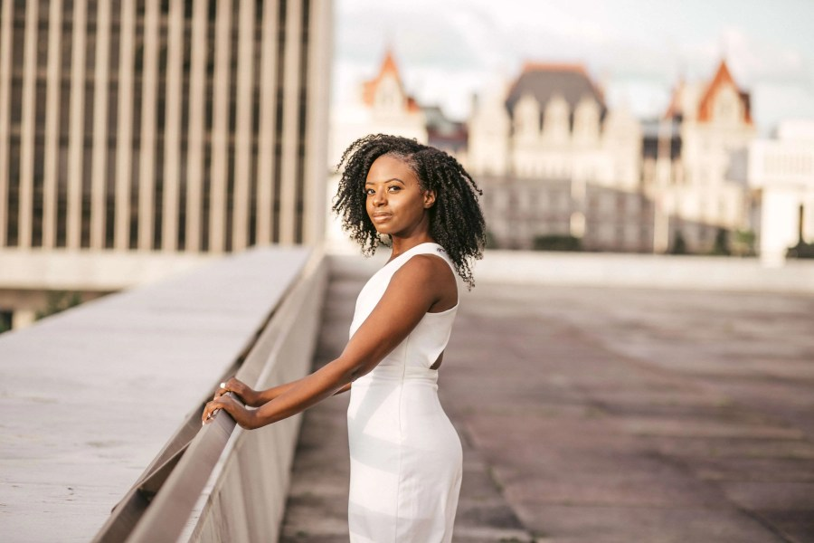 Young woman standing in Empire State Plaza in Albany wearing a white dress and smiling at the camera