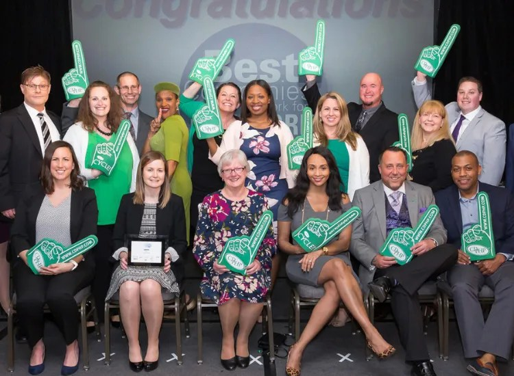 A group of CDPHP employees stand and sit with foam fingers celebrating an award they won.