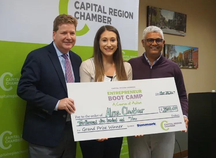 Capital Region President stands with two people and holds a large check donation.