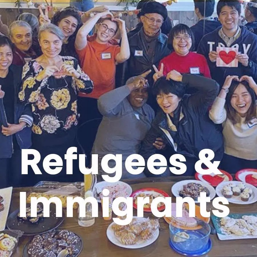 """A group of people pose for the camera in front of a table full of food with the words """"Refugees & Immigrants"""" across the photo."""