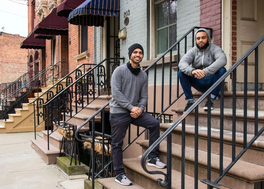Two gentlemen are on the front steps of a brownstone (one standing, one sitting) that they just purchased as an investment property.