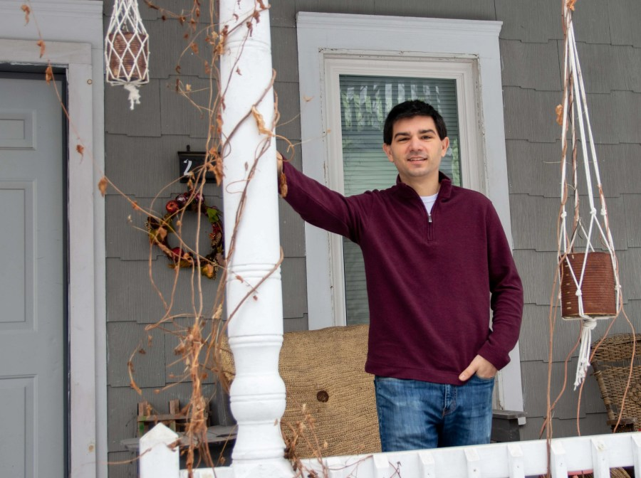 A man in casual attire stands on home's front porch.