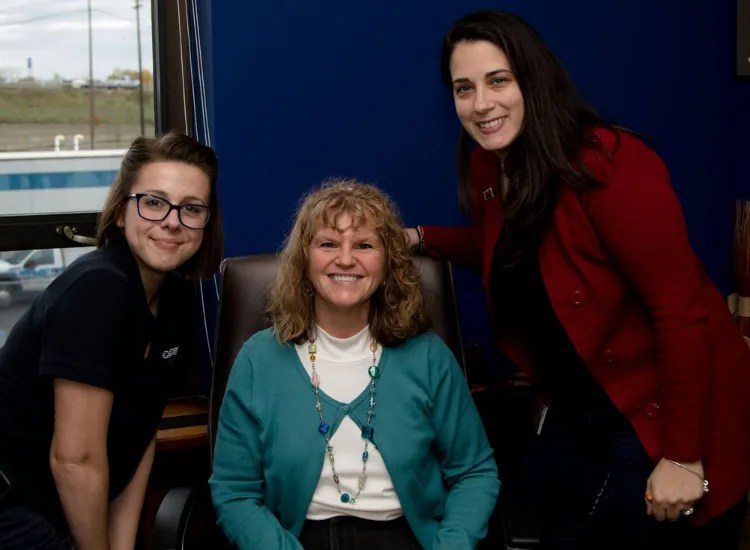Three businesswomen smile at the camera from an office at CDTA