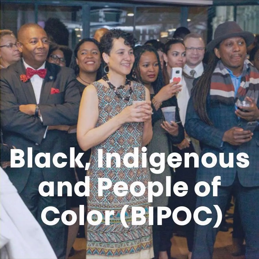 """A group of people stand in a group all looking at something off-camera with the words """"Black, Indigenous and People of Color (BIPOC)"""" across the photo."""
