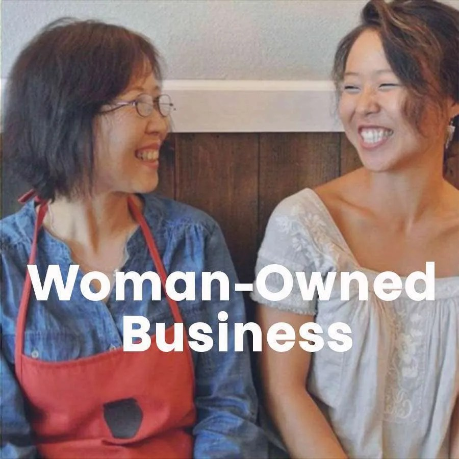 Two women are seated and smiling at each other with the words Woman-Owned Business across the photo