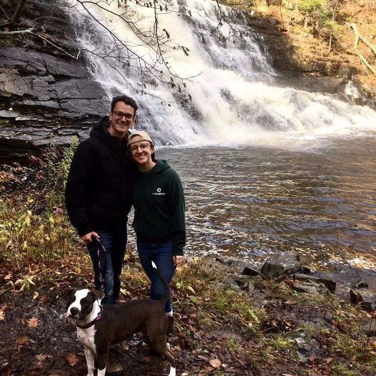 A couple stands in front of a waterfall