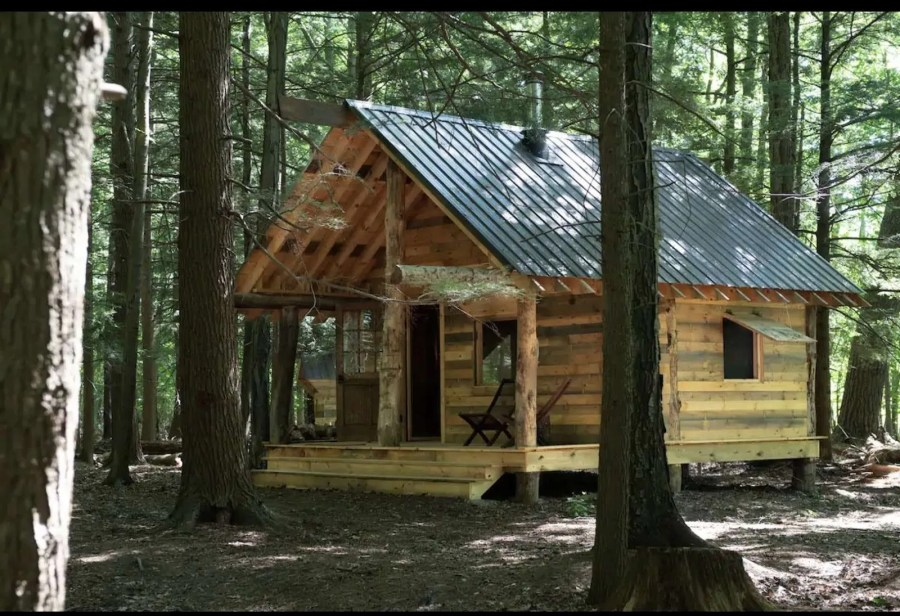 A lone wooden cabin sits in the woods with a chair on the porch.