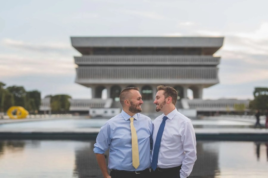 A gay couple smiles at each other as they stand in Empire State Plaza in Albany, NY.