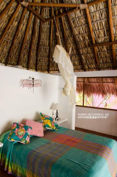 Queen Sized Bed Under a Thatched Roof