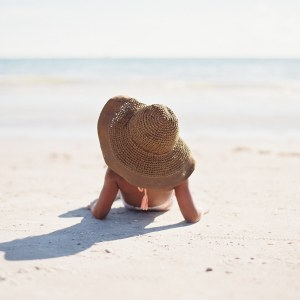 I will reach out to Him for healing. Understanding God's love. God heals us. Unknown woman on beach sun tanning with a wide hat. Synonymous with woman with issue of blood in Bible who is unknown.
