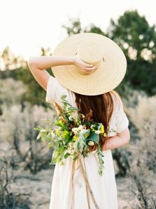 Godly Woman Characteristic – Adorns herself appropriately. 1 Timothy 2:9. Pretty woman in wide hat with light pink dress and flower floral bouquet behind her back.