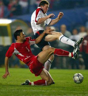 Alpay Özalan s'amuse avec Wayne Rooney. (Source : Adrien Dennis/AFP)