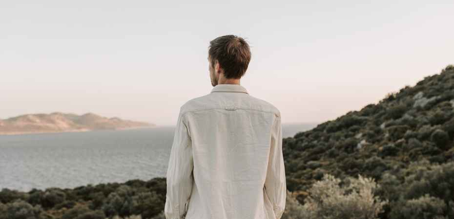 man standing on mountain looking at the sea