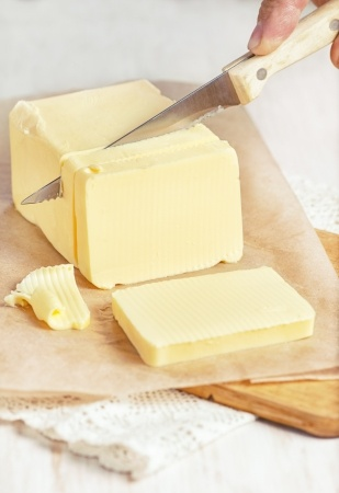 piece of butter on paper cutting by knife