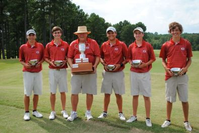 Golf team stands with trophy and bowls they won during the tournament.