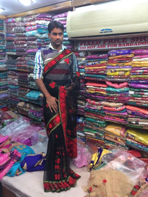 A shop owner explains embroidery details while displaying various styles of sarees.