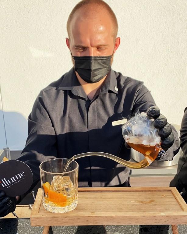 Illume at JW Marriott Bonnet Creek Bartender prepares Smoked Old Fashioned