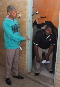 TOTALLY DESTROYED: Ruben Sylvester (SGB deputy chair) points out where criminals gained entry to the school. SGB chair Thanduxolo Joseph Faku crouches to get through the damaged doorway