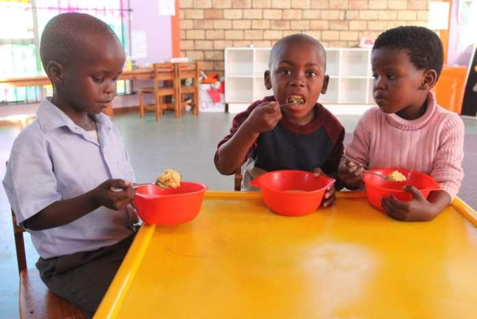 BRIGHTER FUTURE: Enjoying JAM porridge, which supplies 75% of recommended daily nutrients required for healthy living, at Sikhulile Daycare Centre in Duncan Village are, from left, Anganathi Bhodusi, Ndabisukile Ngcali and Popo Onwaba Picture: SARAH KINGON