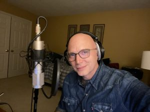 Michael Cerveris in front of a microphone with his headphones on