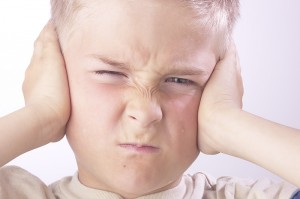 upset child with hands over ears