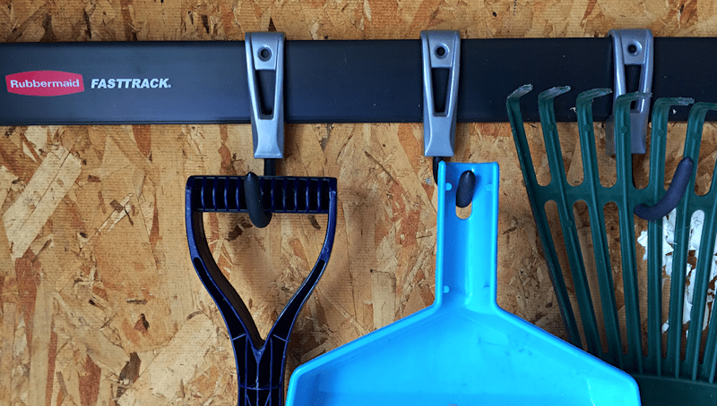 rubbermaid fasttrack garage organizer installed with tools hanging from hooks