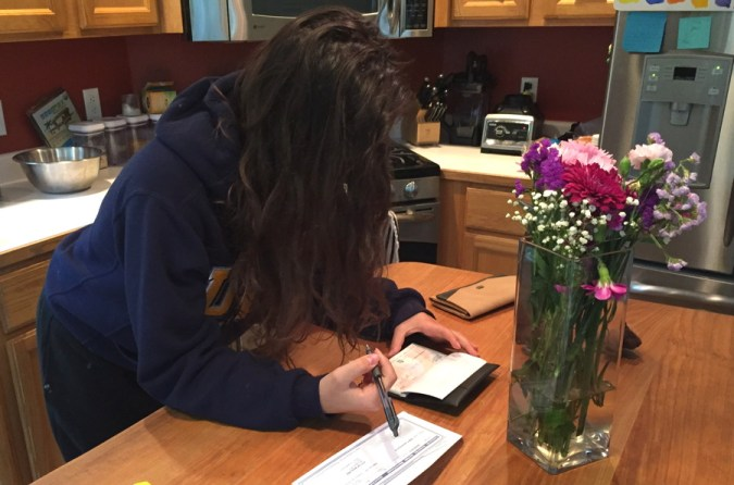 girl writing checks on kitchen counter