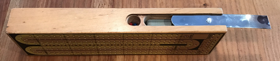wooden cribbage board, at angle with storage