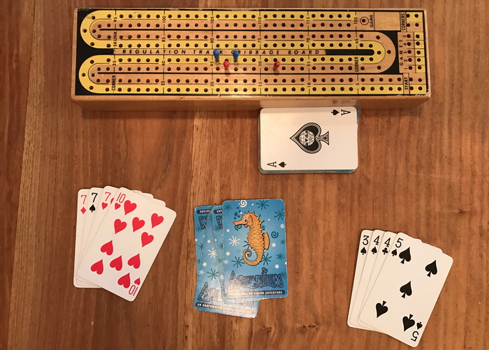 two cribbage hands, ace up as starter plus cribbage board
