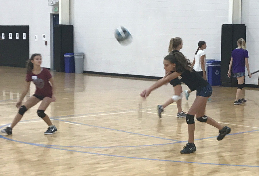 girl sets ball, volleyball camp